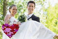 Zusammengesetztes Bild der tragenden Braut des Bräutigams im Garten Stockbilder