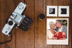 Zusammengesetztes Bild des älteren Mannes einen Kuss und ein Weihnachtsgeschenk gebend seiner Frau Stockfotografie