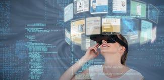 Zusammengesetztes Bild des Abschlusses oben der Frau, die Kopfhörer 3d der virtuellen Realität verwendet Lizenzfreie Stockfotografie