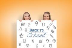 Zusammengesetztes Bild des Abschlusses oben der jungen Frauen hinter einem leeren Zeichen Lizenzfreie Stockfotos