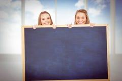 Zusammengesetztes Bild des Abschlusses oben der jungen Frauen hinter einem leeren Zeichen Stockbild