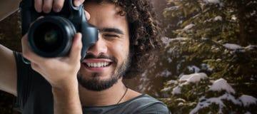 Zusammengesetztes Bild des Abschlusses oben des glücklichen Mannes, der mit Kamera fotografiert Stockfotografie