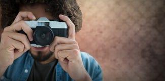 Zusammengesetztes Bild des Abschlusses oben des Mannes, der mit Kamera fotografiert Lizenzfreie Stockfotografie