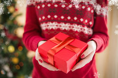 Zusammengesetztes Bild des Abschlusses oben einer Frau, die ein Geschenk anbietet Stockbild