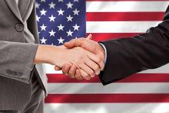Zusammengesetztes Bild des Abschlusses oben von zwei Wirtschaftlern, die ihre Hände rütteln lizenzfreie stockfotografie