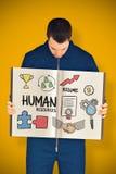 Zusammengesetztes Bild des Arbeiters ein Buch zeigend Stockfotografie