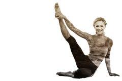 Zusammengesetztes Bild des athletischen blonden Sitzens auf dem Boden, der das Bein oben lächelt an der Kamera ausdehnt Lizenzfreie Stockfotos
