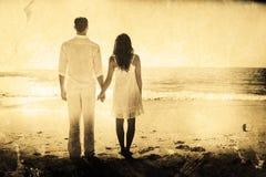 Zusammengesetztes Bild des attraktiven Paarhändchenhaltens und -c$aufpassens der Wellen Stockfotografie