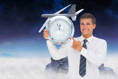 Zusammengesetztes Bild des besorgten Geschäftsmannes eine Uhr halten und zeigend Stockfotografie