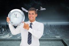 Zusammengesetztes Bild des besorgten Geschäftsmannes eine Uhr halten und zeigend Stockfotos
