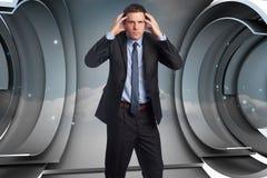 Zusammengesetztes Bild des betonten Geschäftsmannes mit den Händen auf Kopf Stockbild