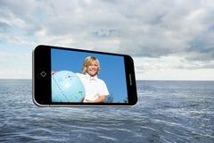 Zusammengesetztes Bild des blonden glücklichen Jungen auf Smartphoneschirm Lizenzfreie Stockfotos