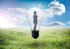 Zusammengesetztes Bild des denkenden Geschäftsmannes in der Glühlampe stockfotos