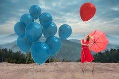 Zusammengesetztes Bild des eleganten blonden haltenen Regenschirmes Lizenzfreie Stockfotos
