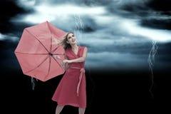 Zusammengesetztes Bild des eleganten blonden haltenen Regenschirmes Stockbilder