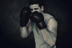 Zusammengesetztes Bild des entschlossenen männlichen Boxers konzentrierte sich auf sein Training Stockfotografie