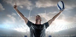 Zusammengesetztes Bild des erfolgreichen Rugbyspielers, der Ball mit den Armen angehoben hält Stockbilder
