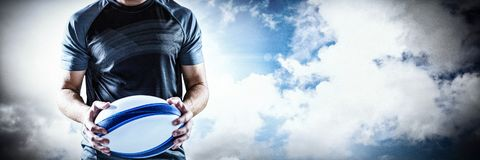 Zusammengesetztes Bild des ernsten Rugbyspielers, der Ball hält lizenzfreie stockfotografie