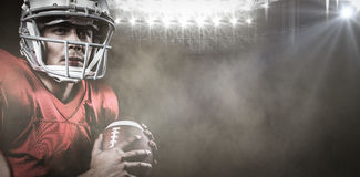 Zusammengesetztes Bild des ernsten Spielers des amerikanischen Fußballs, der beim Halten des Balls weg schaut lizenzfreie stockfotografie