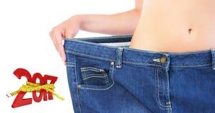 Zusammengesetztes Bild des Extremabschlusses oben der überzeugten schlanken Blondine, die zu große Hose trägt Lizenzfreie Stockfotografie