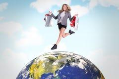Zusammengesetztes Bild des festlichem blondem Springens mit Einkaufstaschen Stockfoto