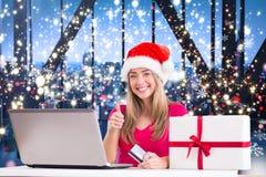 Zusammengesetztes Bild des festlichen blonden Einkaufens online mit Laptop Lizenzfreie Stockfotos