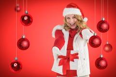 Zusammengesetztes Bild des festlichen blonden haltenen des Weihnachtsgeschenks und -c$zeigens ihres Fingers Lizenzfreies Stockfoto