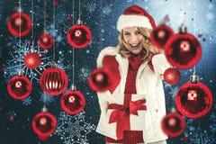 Zusammengesetztes Bild des festlichen blonden haltenen des Weihnachtsgeschenks und -c$zeigens ihres Fingers Stockfotografie