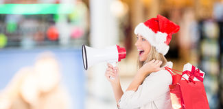 Zusammengesetztes Bild des festlichen blonden haltenen Megaphons und der Taschen Lizenzfreie Stockfotos