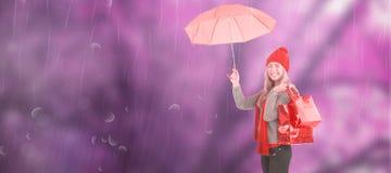Zusammengesetztes Bild des festlichen blonden haltenen Regenschirmes und der Taschen Stockbilder