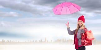 Zusammengesetztes Bild des festlichen blonden haltenen Regenschirmes und der Taschen Stockfotos