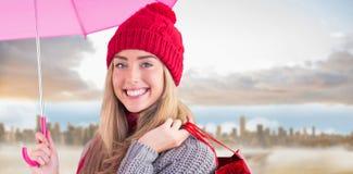 Zusammengesetztes Bild des festlichen blonden haltenen Regenschirmes und der Taschen Lizenzfreie Stockfotos