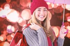 Zusammengesetztes Bild des festlichen blonden haltenen Regenschirmes und der Taschen Lizenzfreie Stockbilder