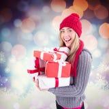 Zusammengesetztes Bild des festlichen blonden haltenen Stapels der Geschenke Lizenzfreie Stockfotos