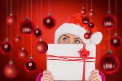 Zusammengesetztes Bild des festlichen blonden haltenen Weihnachtsgeschenks Lizenzfreie Stockfotos