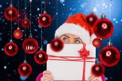 Zusammengesetztes Bild des festlichen blonden haltenen Weihnachtsgeschenks Stockbild