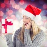 Zusammengesetztes Bild des festlichen blonden haltenen Weihnachtsgeschenks Stockfotos