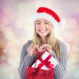 Zusammengesetztes Bild des festlichen blonden haltenen Weihnachtsgeschenks und -tasche Lizenzfreie Stockfotos