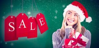 Zusammengesetztes Bild des festlichen blonden haltenen Weihnachtsgeschenks und -tasche Stockbild