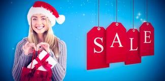 Zusammengesetztes Bild des festlichen blonden haltenen Weihnachtsgeschenks und -tasche Lizenzfreie Stockfotografie
