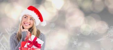 Zusammengesetztes Bild des festlichen blonden haltenen Weihnachtsgeschenks und -tasche Stockfotografie