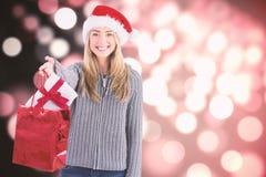 Zusammengesetztes Bild des festlichen blonden haltenen Weihnachtsgeschenks und -tasche Stockbilder