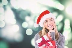 Zusammengesetztes Bild des festlichen blonden haltenen Weihnachtsgeschenks und -tasche Stockfoto