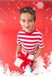 Zusammengesetztes Bild des festlichen kleinen Jungen, der ein Geschenk hält Stockfoto