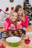 Zusammengesetztes Bild des festlichen kleinen Mädchens, das Weihnachtsplätzchen macht Lizenzfreies Stockfoto