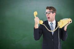 Zusammengesetztes Bild des geeky Geschäftsmannes schreiend am Telefon Stockfotografie
