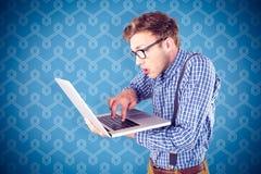 Zusammengesetztes Bild des geeky Geschäftsmannes unter Verwendung seines Laptops Lizenzfreie Stockfotografie