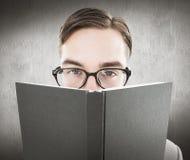 Zusammengesetztes Bild des geeky Mannes schauend über Buch Lizenzfreie Stockbilder