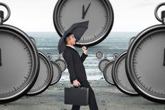 Zusammengesetztes Bild des Geschäftsmannes den Wind mit Regenschirm drückend Lizenzfreie Stockfotografie