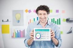 Zusammengesetztes Bild des Geschäftsmannes digitale Tablette mit leerem Bildschirm im kreativen Büro zeigend Lizenzfreies Stockfoto